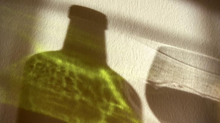 Skygger av flaske og glass på hvit bakgrunn