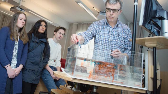 Helge Drange viser eksperiment med vanntank for tre elever