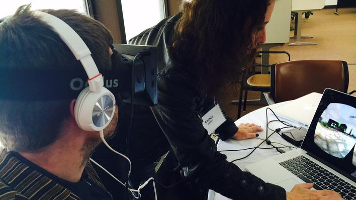 A man wearing an Oculus Rift visor and headphones experiences a work of electronic literature at ELO2014.