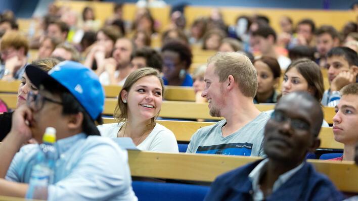 Auditorium med mange studenter og to som ser smilende på hverandre i fokus