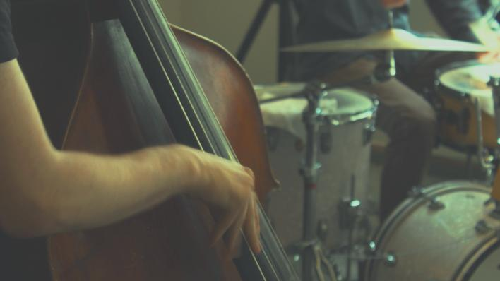 illustrasjonsbilde: i forgrunnen en underarm og et utsnitt av en kontrabass, i bakgrunnen et slagverk