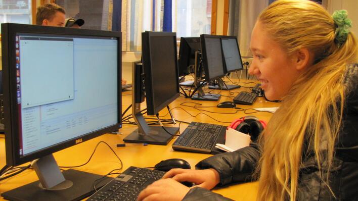 En jente spiller engasjert foran datamaskinen