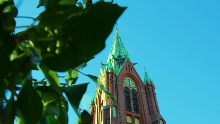 bilete av tårnet til johanneskyrkja mot blå himmel og grønn eføy til venstre i bildet