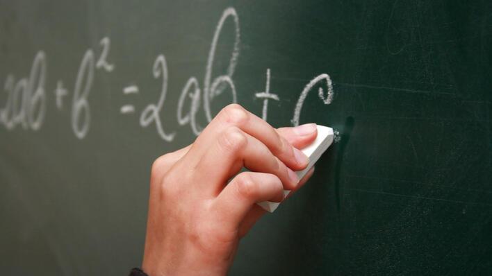 Hånd som skriver på en tavle