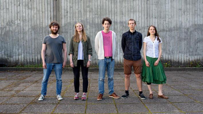 fem mennesker foran betongvegg