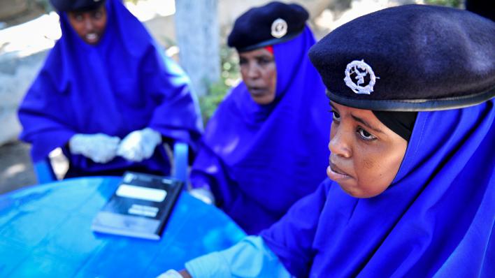 Somalske politistudiner med beret sit rundt eit blått plastbord i knallblå drakter.