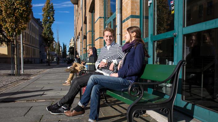 Studenter drikker kaffe i solskinnet på en benk utenfor SV-fakultetet