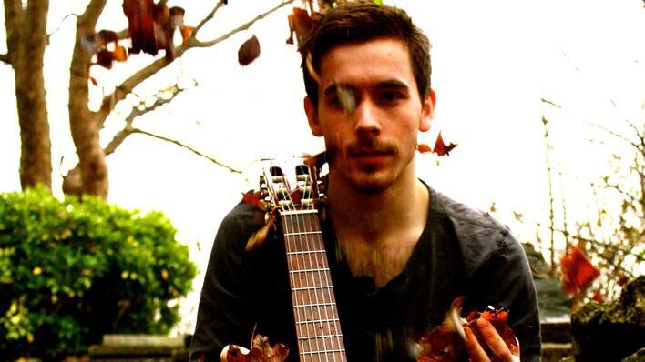 portrettbilde av svein gustav hoff som kaster høstløv i luften mens han har en gitar hvilende mot høyre skulder