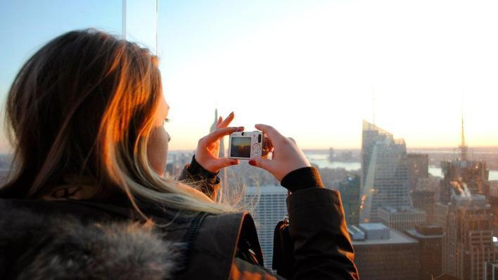 Jente tar bilde gjennom et vindu høyt oppe av en by med høyhus.