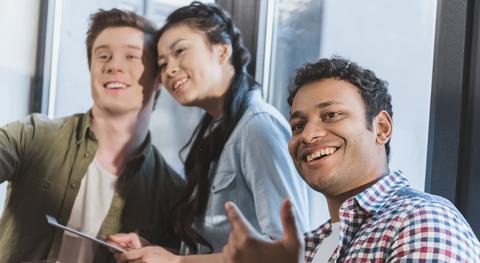 Two men and a woman of different ethnic origin smiling
