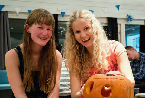 To kvinnelige studenter smiler til kamera med et gresskar foran