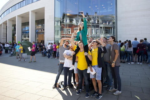 Students in front of the Student Centre standing in a group, carrying one student who's taking a selfie of all of them