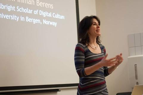 Kathi Inman Berens står foran et lerret og foreleser.