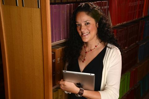 Photograph of Mia Zamora holding an iPad in a library.