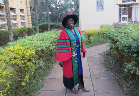 Perpetra Akite standing in her graduation gown at the ceremnony of her PhD graduation