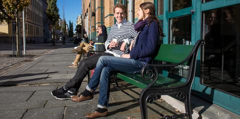 Two students having coffee on a bench outside the faculty building in the sun.