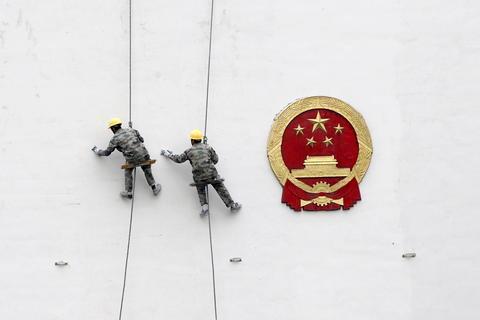 Arbeidere maler en regjeringsbygning i byen Hangzhou i Zhejiang-provinsen i Kina.