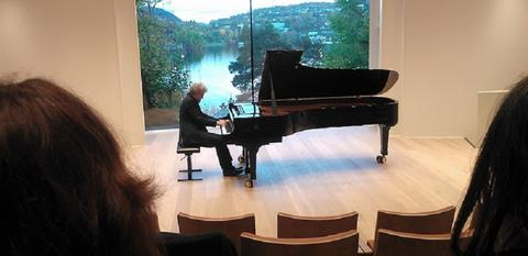 A person is playing piano in a consert hall