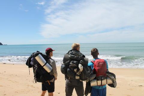 Tre studenter med ryggsekker på en strand på New Zeland.