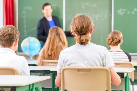Bilde av lærer ved tavlen i klasserom