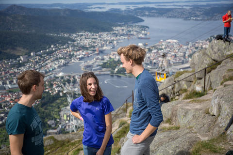 Three students on top of Mount Ulriken with Bergen in the background