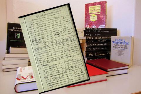 Bilde av Wittgensteins Nachlass sammen med en rekke av Wittgensteins publikasjoner og med utdrag fra håndskrevet manus som bildet i forkant.