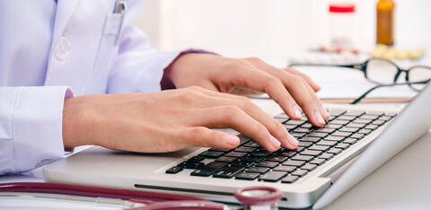 a doctor writing on a laptop.