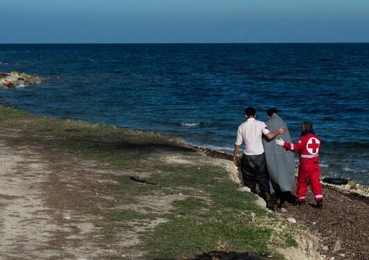 Tre mennesker går langs en strand, en person har et grått teppe over seg og er flankert i en person i Røde Kors-uniform på høyre side og en mann i hvit skjorte på venstre side.