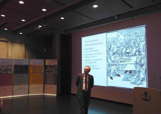 Bilde av Jens Eike Schnall under foredraget med plakatene om mat i bakgrunn
