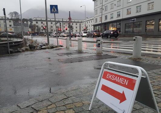 Bilde fra utemiljø utenfor nytt eksamenslokale på Danmarksplass, med skilt med teksten EKSAMEN i rødt.