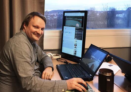 Mann sitter ved PC med vindu i bakgrunnen