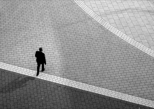 Mann som går over en strek på et torg, fotografert ovenfra.