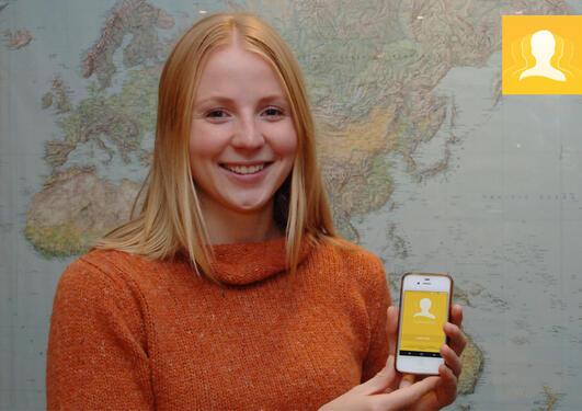 Kvinnelig student viser frem en mobil med studentbevislogoen