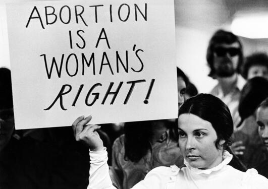 Woman holding a poster on women's right to abortion