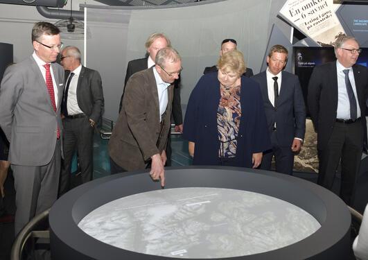 Professor Anders Lundberg forklarer statsminister Erna Solberg og rektor Dag Rune Olsen hvordan stasjonen Folk og landskap er utformet.
