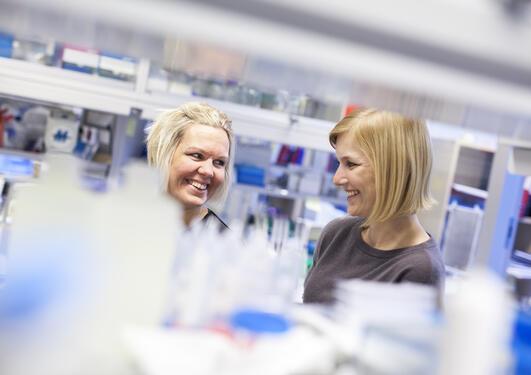 to kvinnelige medarbeidere smiler til hverandre på lab