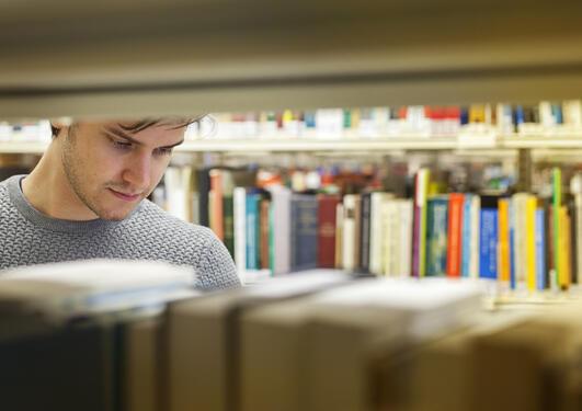 Student leser i bøker på Det juridiske fakultet
