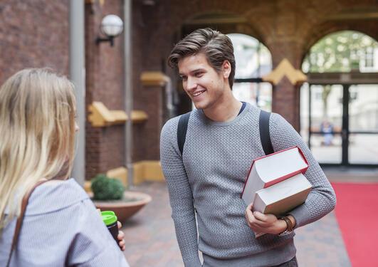 Jusstudenter med bøker ved hovedinngangen på jussen