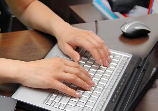 Kvinnehender som skriver på en datamaskin
