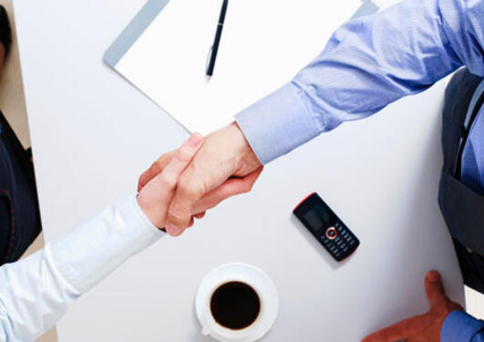 2 business people shaking hands over a contract