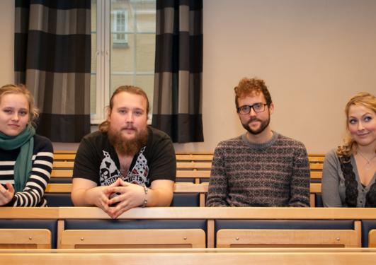 Fire sittande studentar ser i kameraet