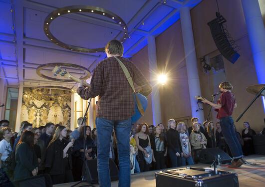 musikere på scenen i aulaen fotografert bakfra med publikum i bakgrunnen av bildet