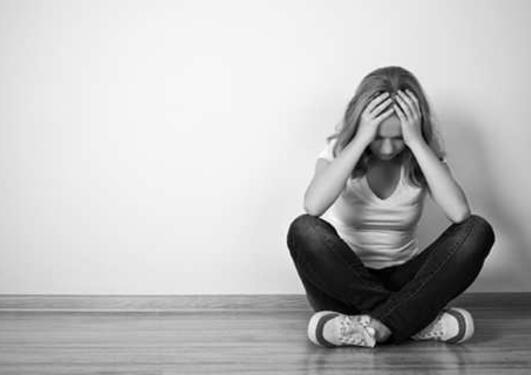 Kvinne som sitter med bena i kors på gulvet, skjuler ansiktet