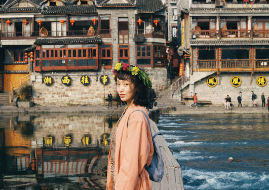 Girl by a river in Fenghuang, China