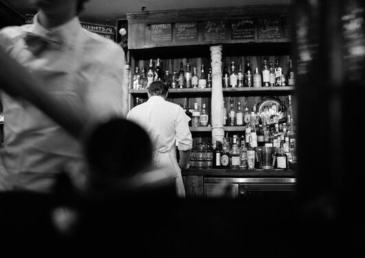 Eit svart-kvitt bilete som viser ein bar, to bartendarar i kvit skjorte der den fremste er litt ute av fokus og kun vist frå halsen og ned