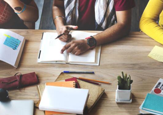 Bilde tatt av bord med skrivebøker. Man ser armene til tre personer som sitter ved bordet.