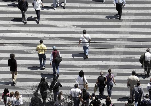 Illustrasjonsfoto av mange mennesker som krysser et stort overgangsfelt i en storby.