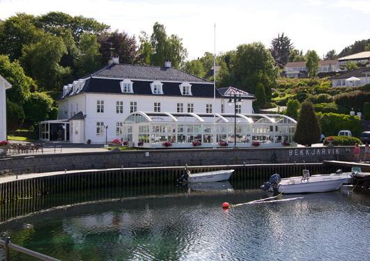 Ein stor, kvit bygning med grøne tre i bakgrunnen, vatn og båtar i framgrunnen