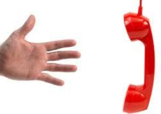 Håns som strekker seg mot et rødt telefonrør