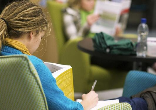 A student reads a book in the library